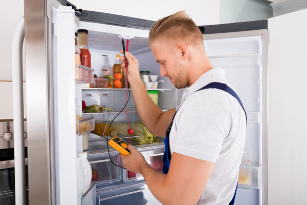70823974 young repairman checking refrigerator with digital multimeter