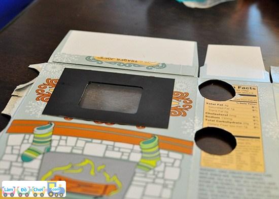 Bước 2: Các mẹ sử dụng một miếng bìa khác hoặc miếng nhựa, có trong các hộp đồ chơi, cắt thành hình ti vi rồi dán đè lên hình chữ nhật vừa cắt ở trên.
