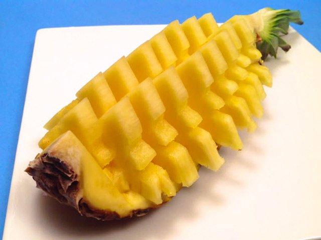 Bạn chia quả dứa thành 4 phần theo chiều dọc. Sau đó dùng dao sắc khoét lấy phần thịt và chia nhỏ thành các miếng vừa ăn
