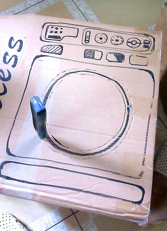 Bước 2: Mẹ rọc theo đường tròn cửa máy giặt đã vẽ, chừa lại không rọc khoảng 5 cm phía bên phải để làm bản lề đóng mở cửa máy giặt. Bôi keo lên mặt trong để dán miếng bìa ni-long làm của kiếng máy giặt.