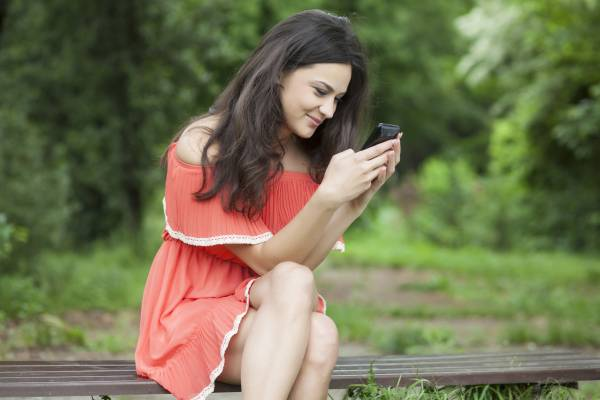girl sitting on a park bench and writes text message